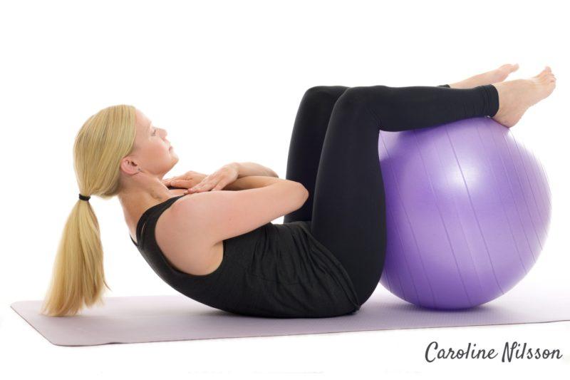 Crunches med fötterna på träningsboll