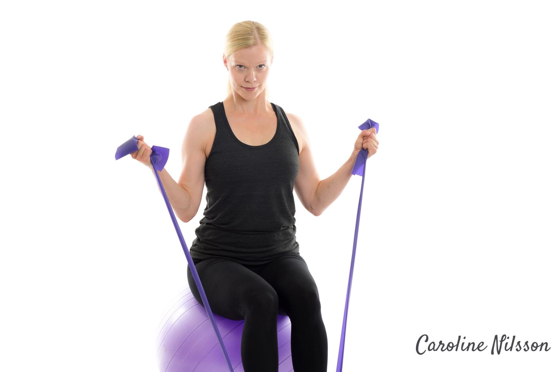 bicepsböj med gummiband sittande på pilatesboll