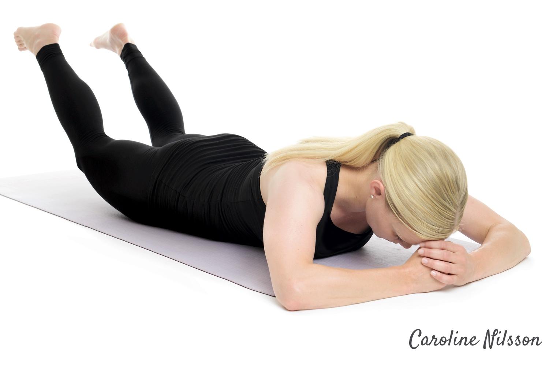 Ligg på mage och lygt benen för att träna ryggens muskler